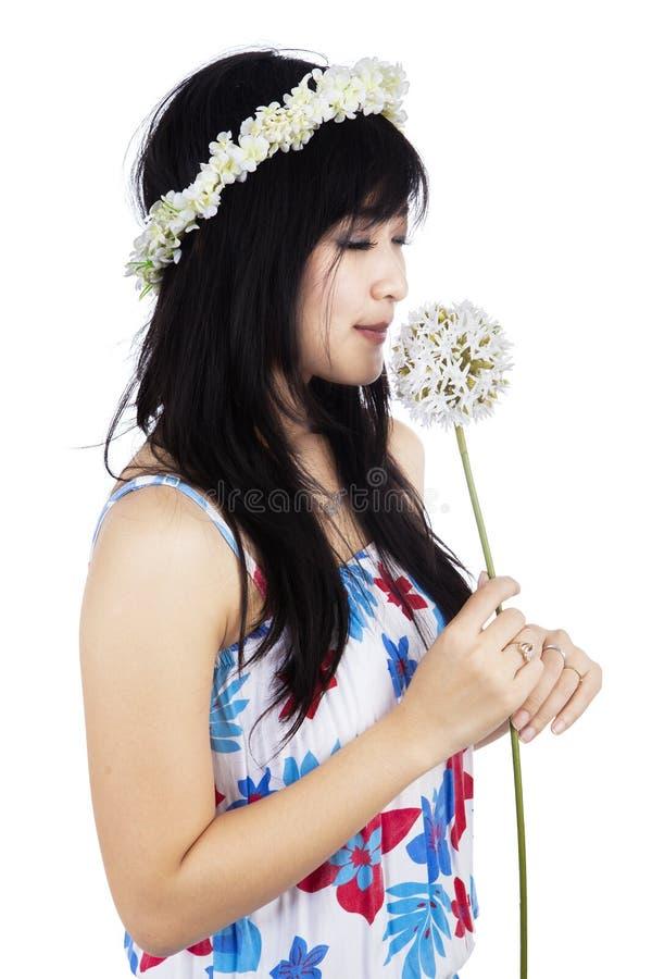 A menina está cheirando uma flor imagens de stock