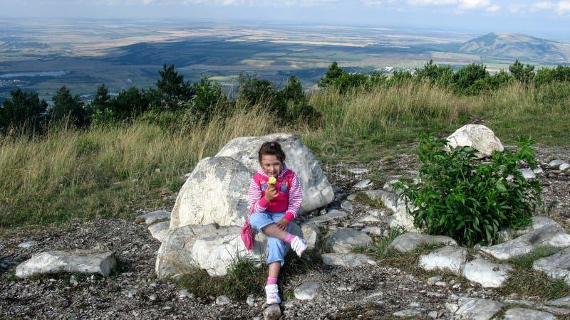 A menina está comendo o gelado na parte superior da montanha em Pyatigorsk imagens de stock royalty free