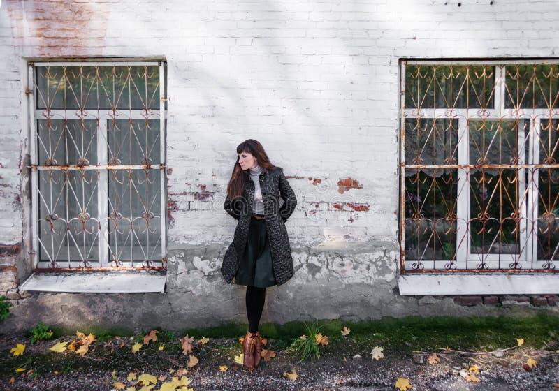 A menina está contra uma parede de tijolo branca imagem de stock