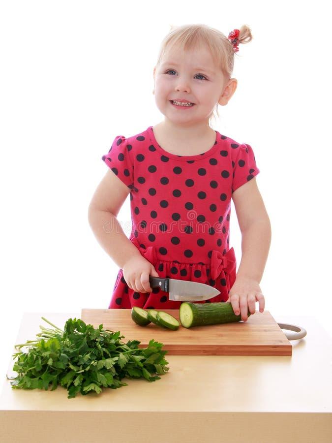 A menina está cortando vegetais com uma faca foto de stock royalty free