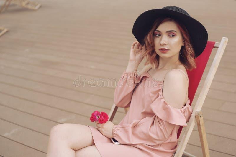 A menina está descansando em um vadio A menina em um vestido cor-de-rosa bonito, chapéu elegante preto está descansando em uma vi foto de stock