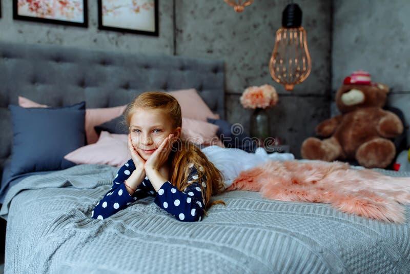 A menina está encontrando-se na cama, sorrindo foto de stock royalty free