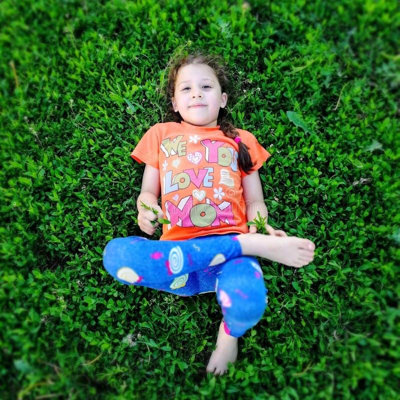 A menina está encontrando-se na grama verde e está olhando-se acima imagem de stock