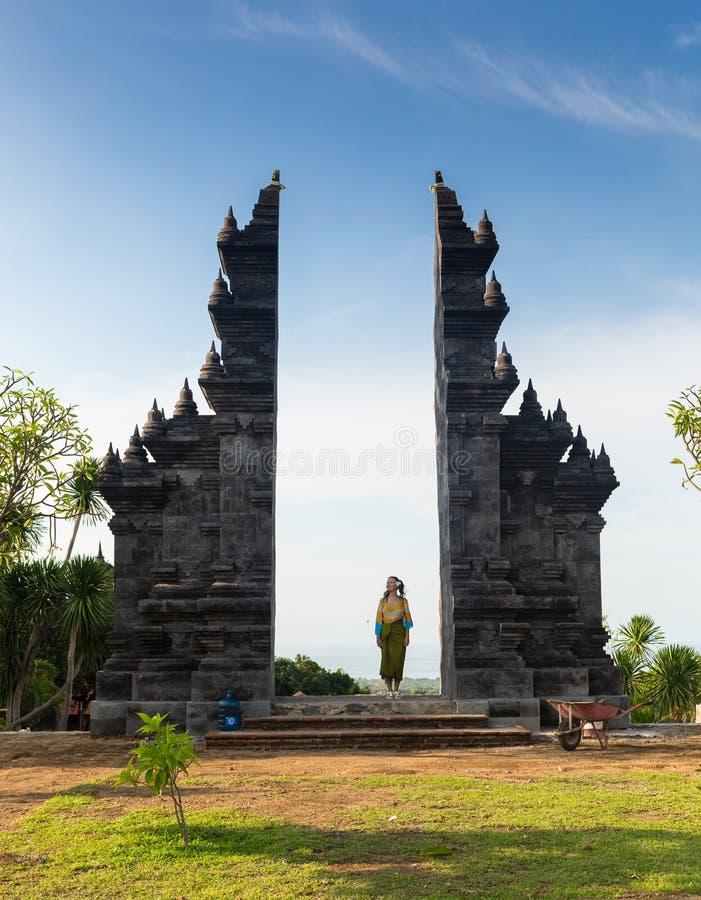 A menina está estando na porta do templo de Pura Lempuyang na ilha de Bali, Indonésia fotos de stock royalty free