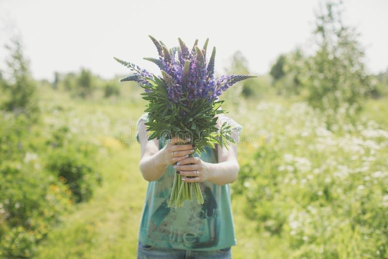 A menina está estando no campo com um ramalhete dos lupines fotos de stock royalty free