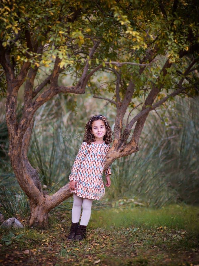 A menina está estando pela árvore fotografia de stock