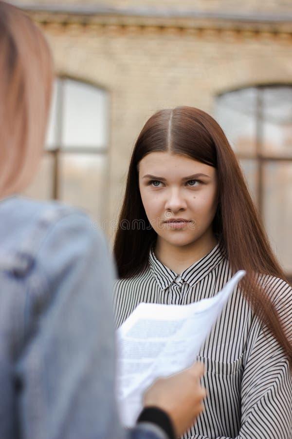 A menina está estando perto da universidade e do olhar no adulto com papel fotos de stock
