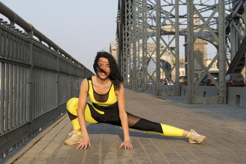 A menina está esticando em uma ponte fora, esportes fotografia de stock
