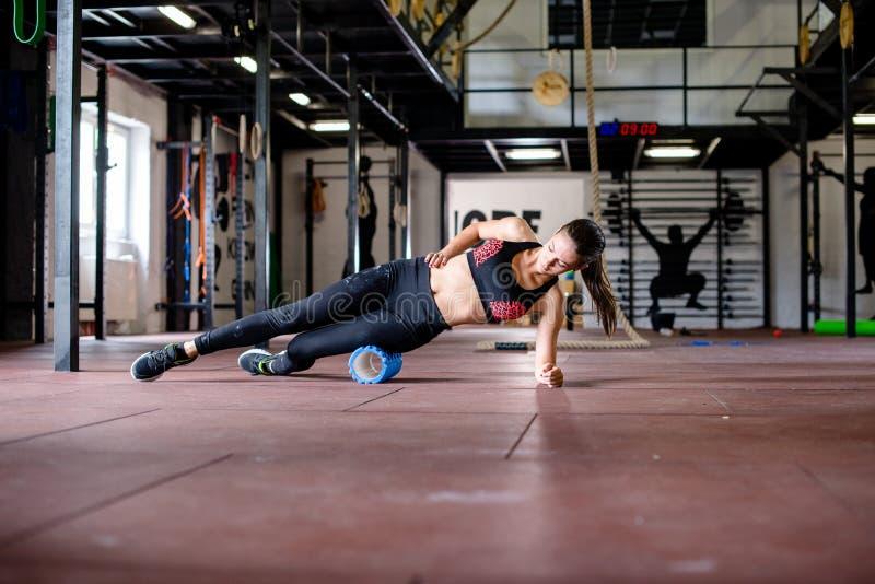 A menina está exercitando no assoalho do gym imagens de stock royalty free