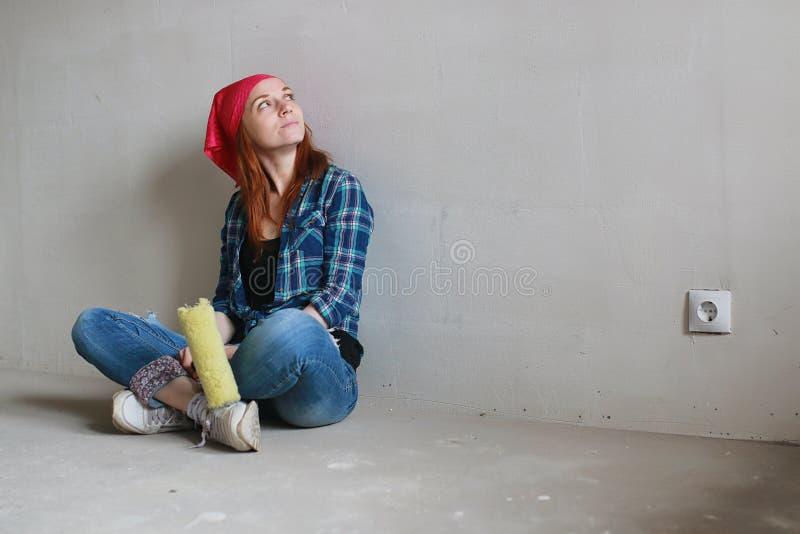 A menina está fazendo reparos no apartamento Mover-se home para um apartamento novo O trabalhador faz os reparos, emplastrados e foto de stock royalty free