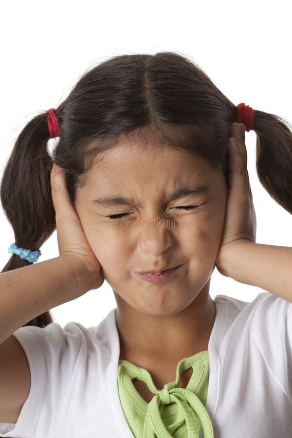 A menina está fechando suas orelhas com suas mãos foto de stock royalty free