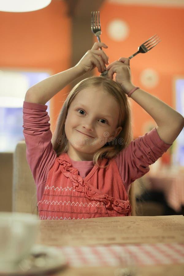 A menina está guardando forquilhas sobre sua cabeça no restaurante imagens de stock royalty free