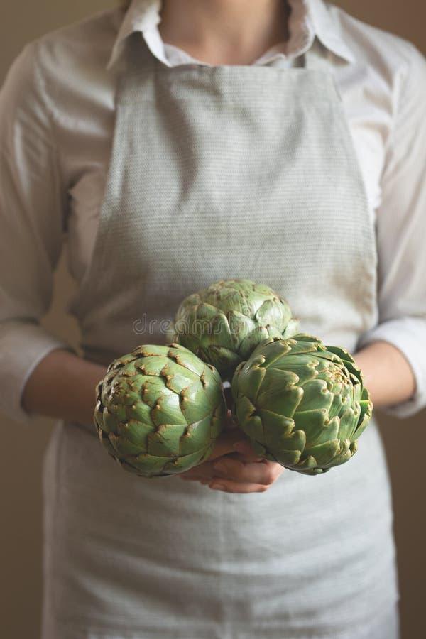 A menina está guardando uma alcachofra em suas mãos Um conceito da nutrição apropriada e dietética, Dotex foto de stock royalty free