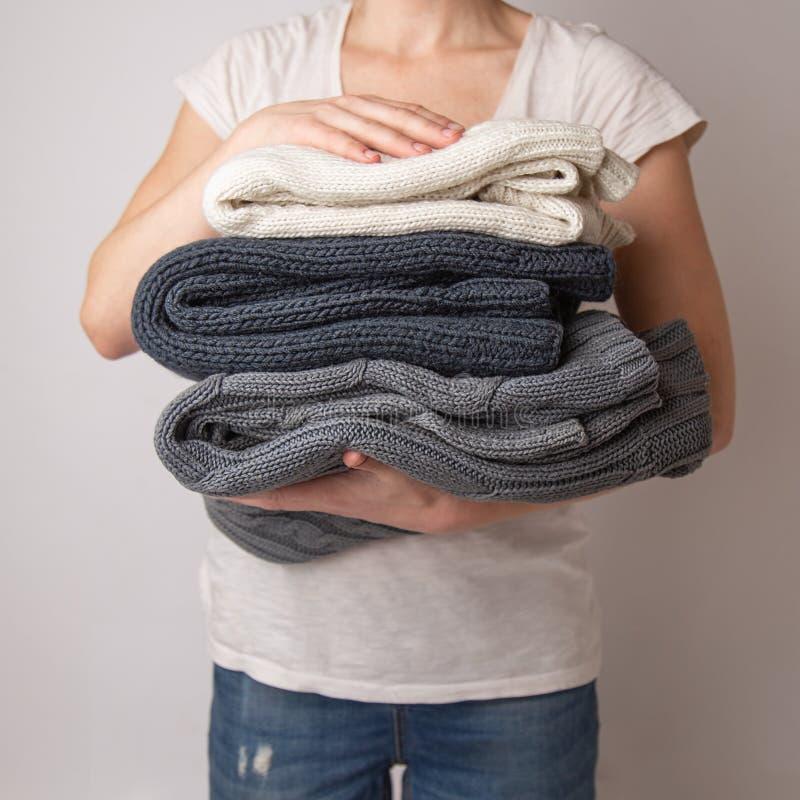 A menina está guardando uma pilha de camisetas feitas malha roupa lavadas e passadas em suas mãos em um fundo branco foto de stock royalty free