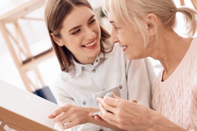 A menina está importando-se com a mulher idosa em casa Estão olhando fotos no álbum de fotografias imagens de stock royalty free