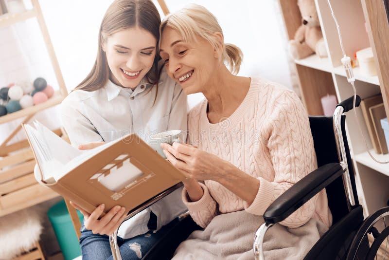 A menina está importando-se com a mulher idosa em casa Estão olhando fotos no álbum de fotografias fotografia de stock