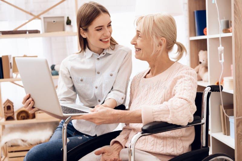A menina está importando-se com a mulher idosa em casa Estão usando o portátil imagem de stock