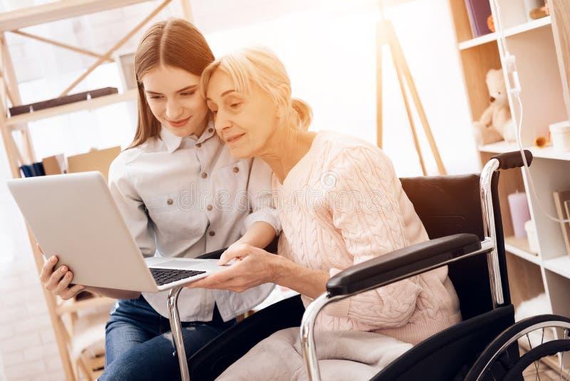 A menina está importando-se com a mulher idosa em casa Estão usando o portátil fotografia de stock
