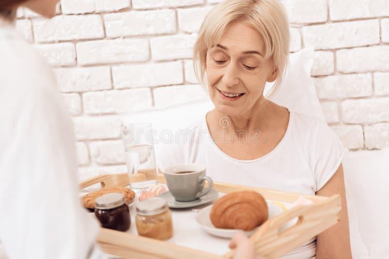 A menina está importando-se com a mulher idosa em casa A menina traz o café da manhã na bandeja fotos de stock royalty free