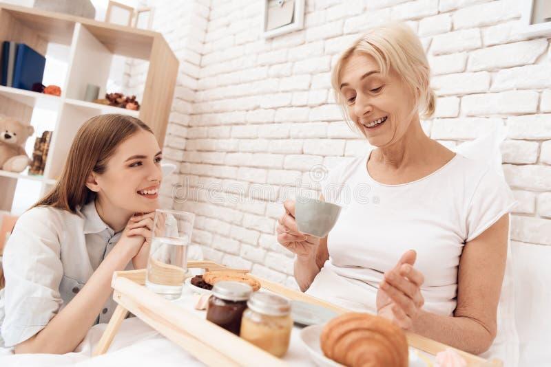 A menina está importando-se com a mulher idosa em casa A menina traz o café da manhã na bandeja fotografia de stock royalty free