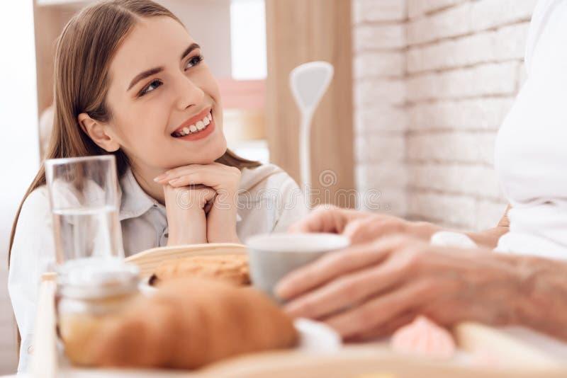 A menina está importando-se com a mulher idosa em casa A menina traz o café da manhã na bandeja A menina está sorrindo foto de stock royalty free