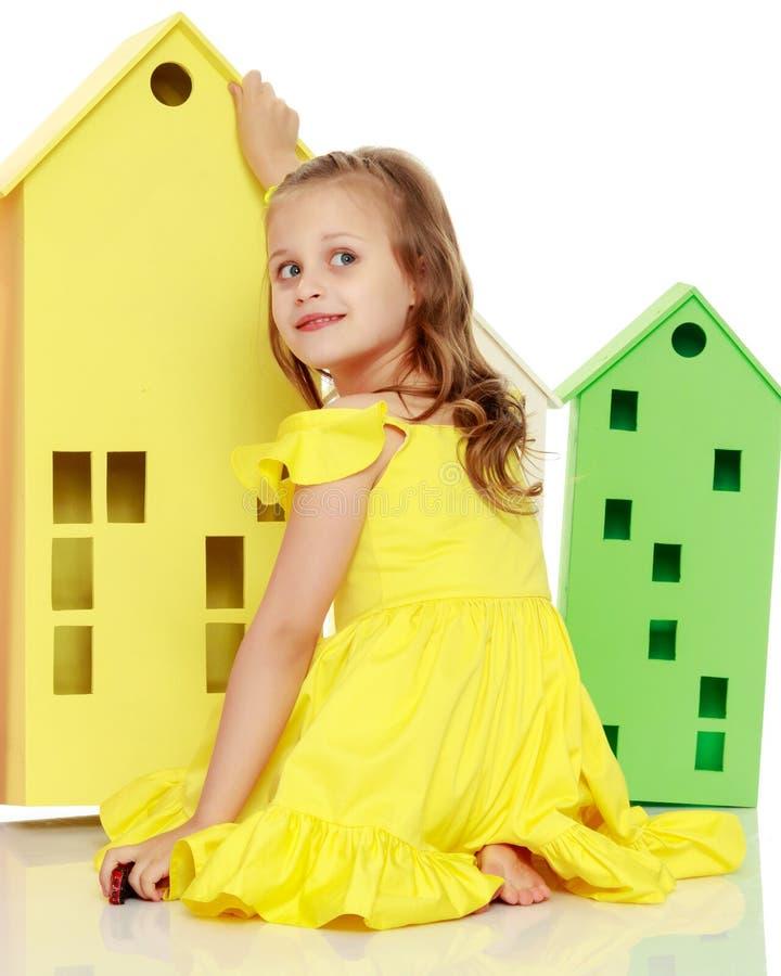 A menina está jogando com casas de madeira imagens de stock royalty free