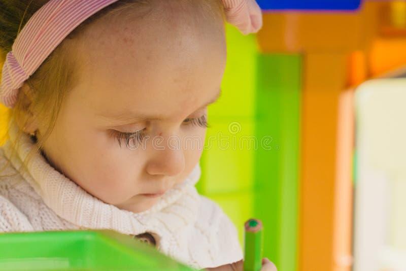 A menina está jogando com os brinquedos na sala do ` s das crianças fotografia de stock