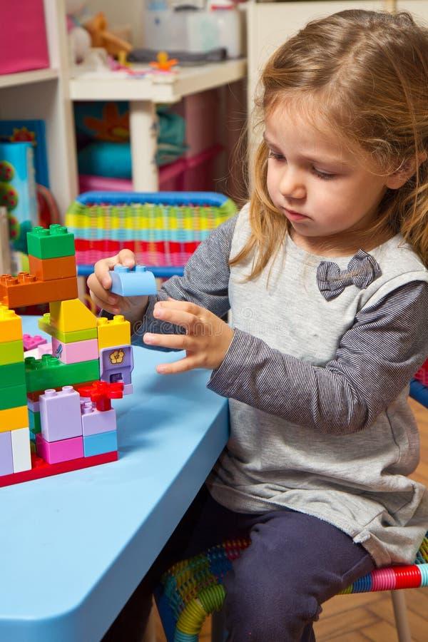 a menina está jogando com tijolos da construção fotos de stock