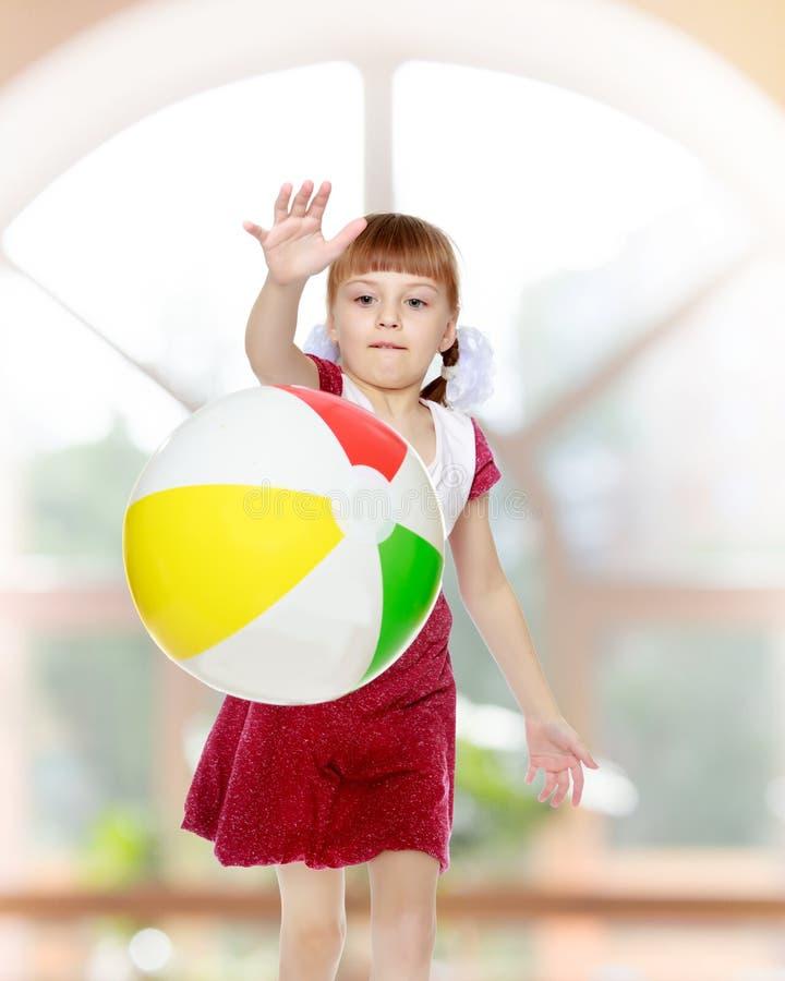 A menina está jogando com uma bola imagens de stock