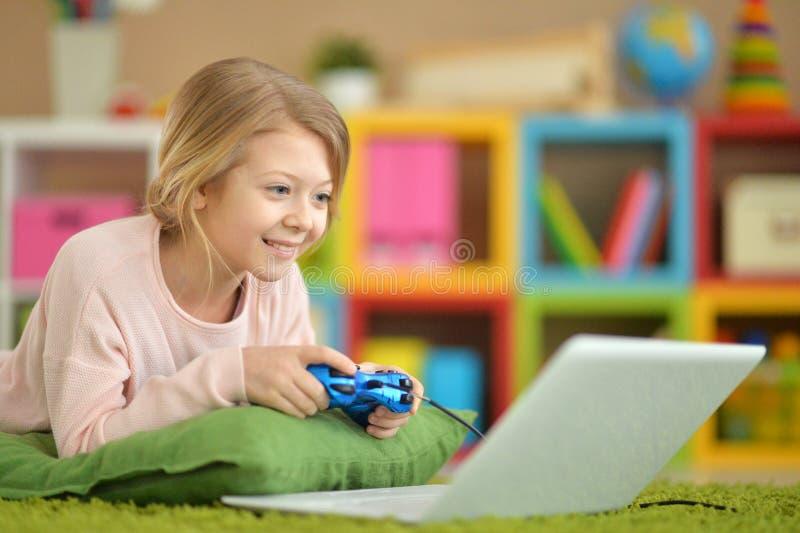 A menina está jogando um jogo de computador fotografia de stock