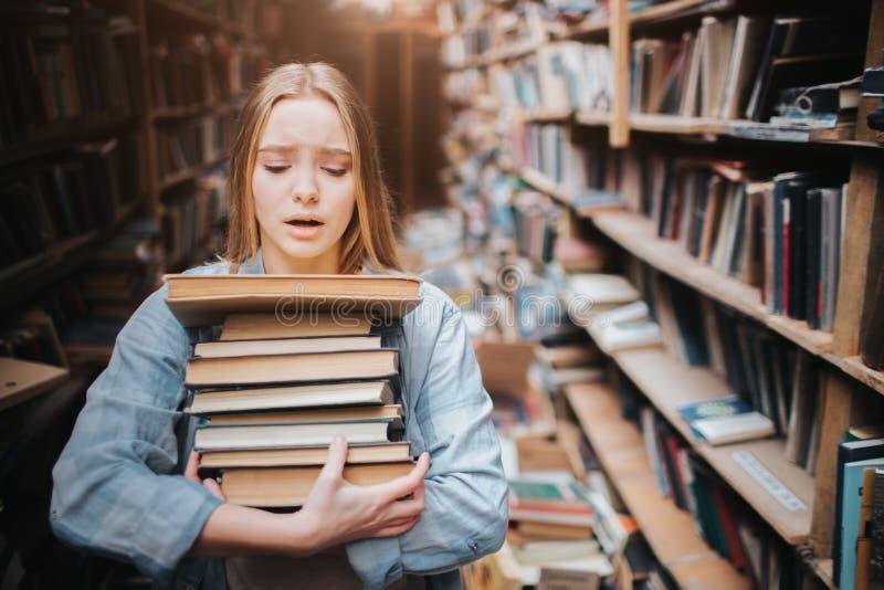 A menina está levando muitos livros em suas mãos É duro para ela fazer Olha hepless e cansado A menina está dentro imagens de stock