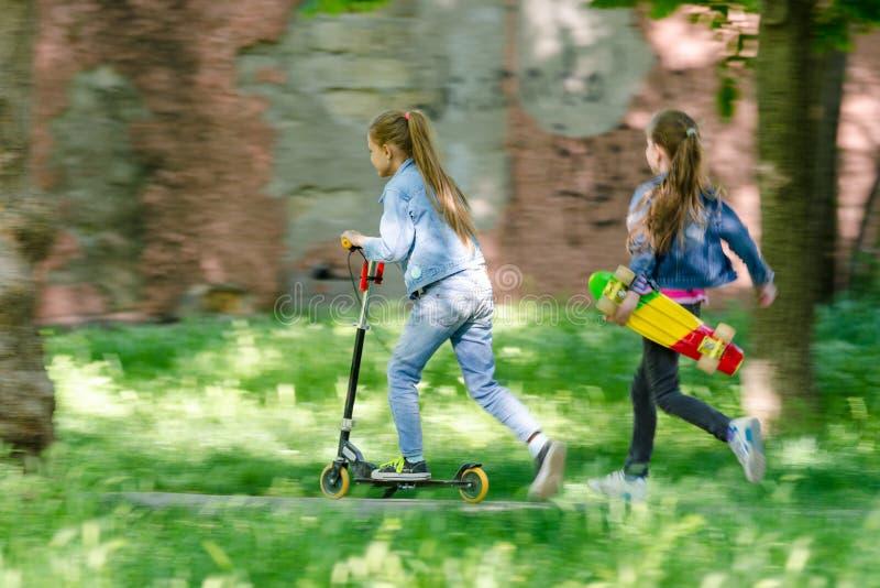 A menina está montando felizmente no 'trotinette', atrás de suas corridas uma outra menina com um patim em suas mãos fotografia de stock royalty free