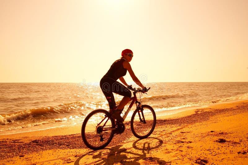 A menina está montando uma bicicleta ao longo da costa de mar arenosa fotos de stock royalty free