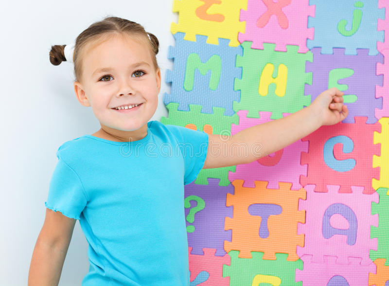 A menina está mostrando a letra E no alfabeto fotos de stock
