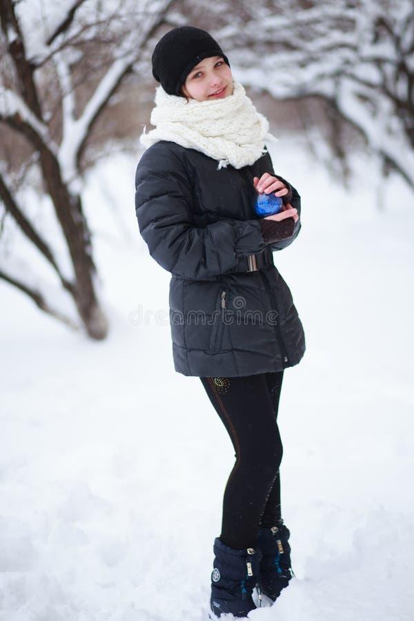 A menina está na perspectiva dos ramos cobertos de neve fotografia de stock