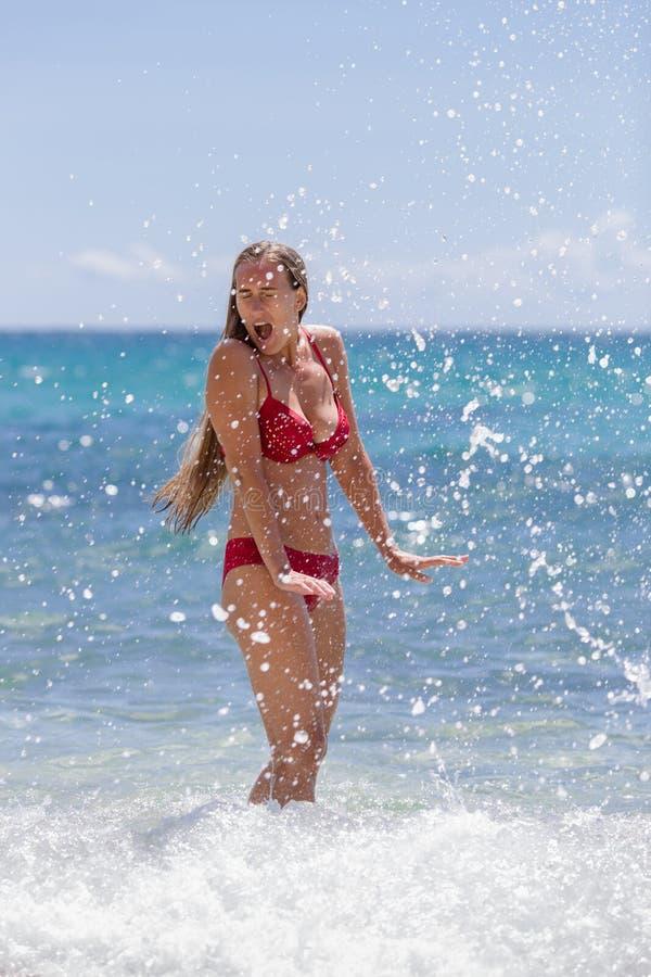 A menina está no seawater, cercado por um pulverizador do seafoam fotografia de stock royalty free