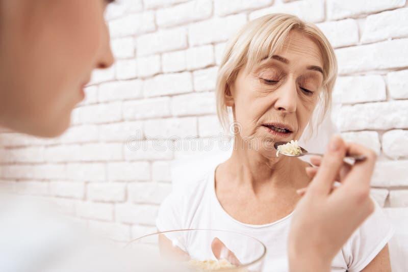 A menina está nutrindo a mulher idosa em casa A menina está ajudando a mulher com alimento fotografia de stock royalty free