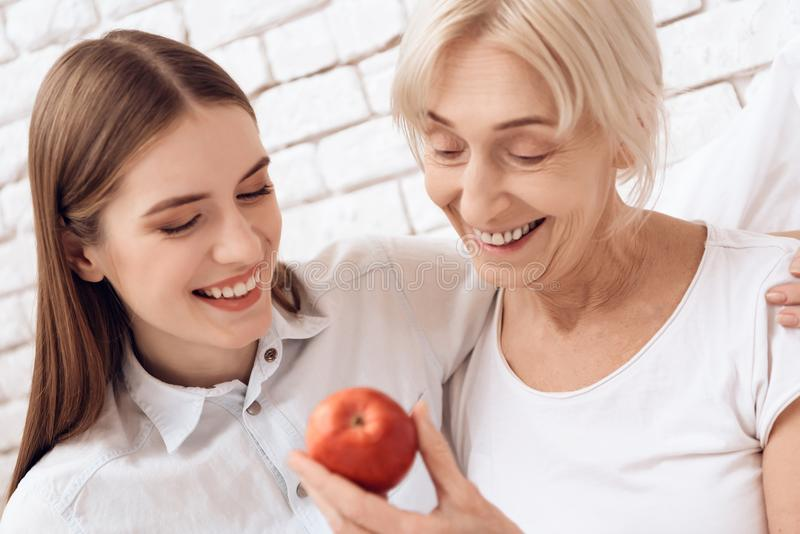 A menina está nutrindo a mulher idosa em casa Estão abraçando A mulher está guardando a maçã fotos de stock