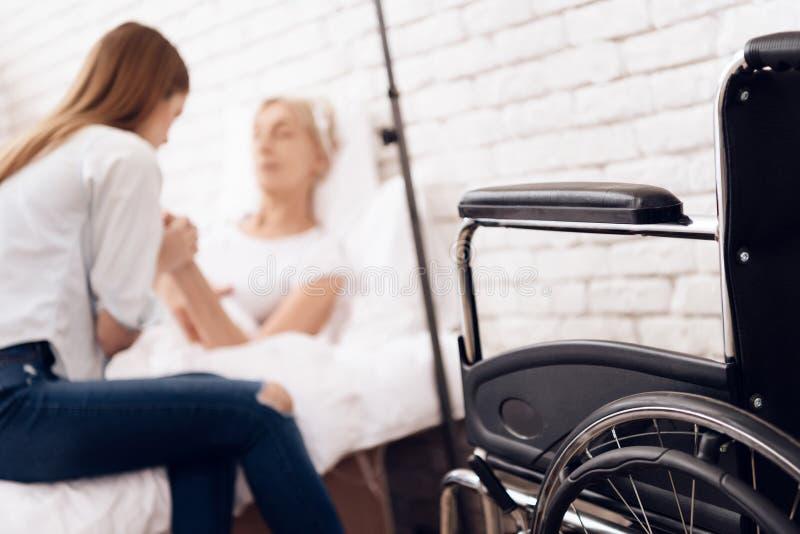 A menina está nutrindo a mulher idosa em casa Estão guardando as mãos A cadeira de rodas está estando próximo fotografia de stock royalty free