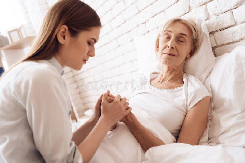 A menina está nutrindo a mulher idosa em casa Estão guardando as mãos A mulher está sentindo mais má foto de stock royalty free