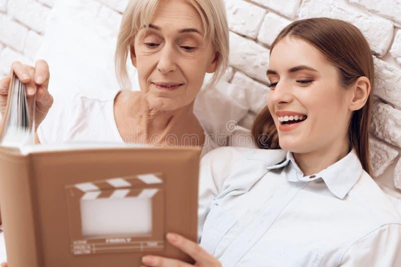 A menina está nutrindo a mulher idosa em casa Estão olhando fotos no álbum de fotografias foto de stock royalty free
