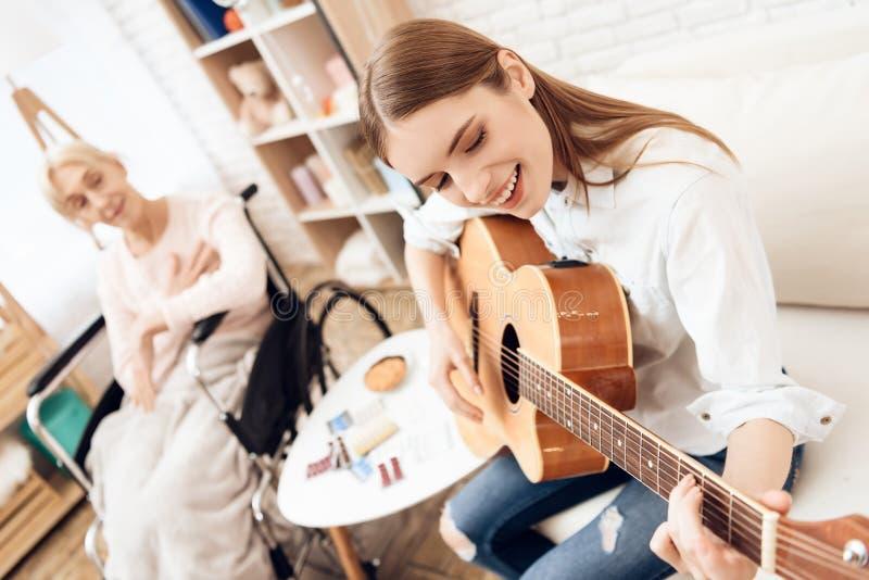 A menina está nutrindo a mulher idosa em casa A menina está jogando na guitarra para a mulher fotos de stock royalty free