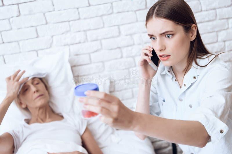 A menina está nutrindo a mulher idosa em casa A menina está no telefone, dando comprimidos à mulher foto de stock royalty free