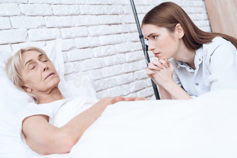 A menina está nutrindo a mulher idosa em casa A mulher está sentindo má, menina é preocupou-se sobre ela fotografia de stock