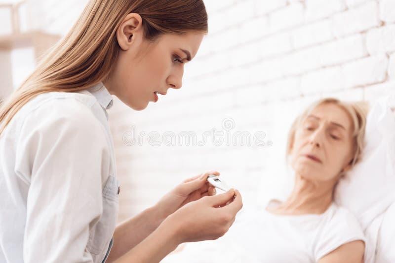 A menina está nutrindo a mulher idosa em casa A menina está verificando a temperatura É infeliz fotos de stock