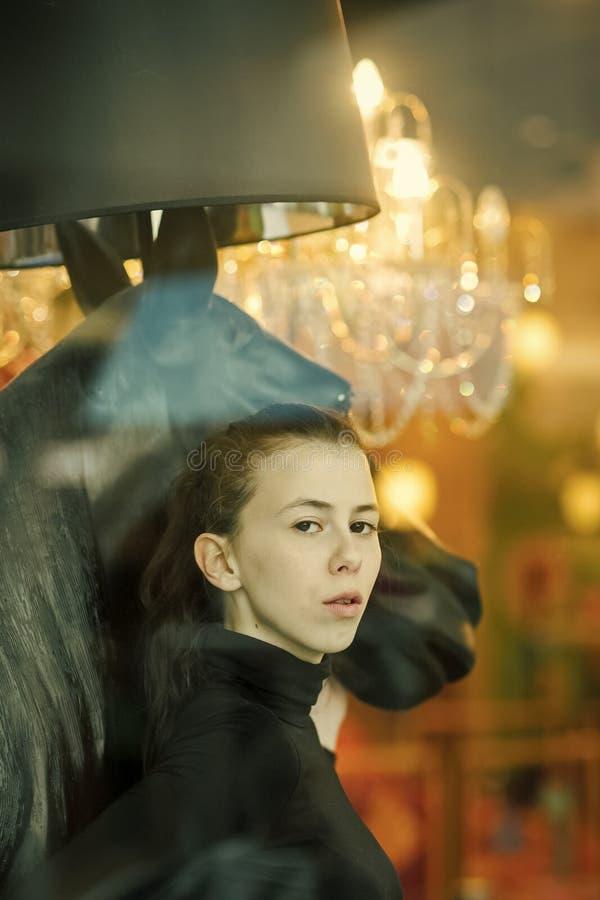 A menina está olhando através da janela A jovem senhora com cara pensativa abraça a cabeça de cavalos Conceito da feminilidade foto de stock royalty free