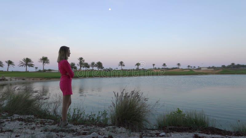 A menina está olhando o jogo no campo de golfe no crepúsculo O suporte da mulher perto da lagoa sob a lua, sonha e pensa buggy video estoque