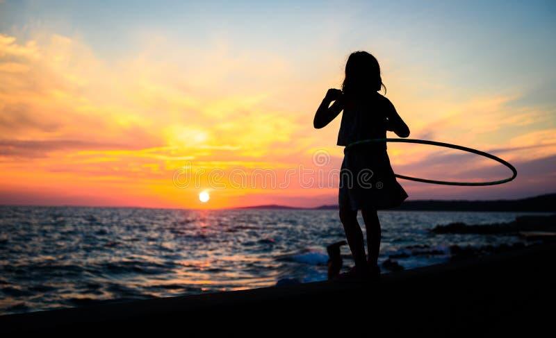 A menina está olhando o por do sol de surpresa do mar com aro do hula foto de stock