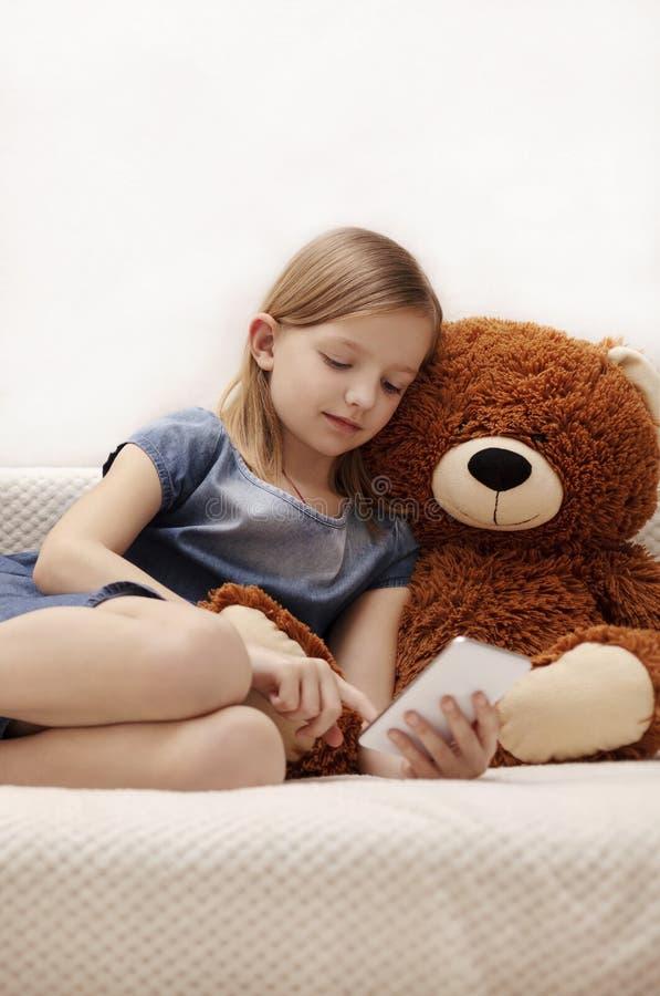 A menina está olhando o smartphone em casa no sofá imagem de stock