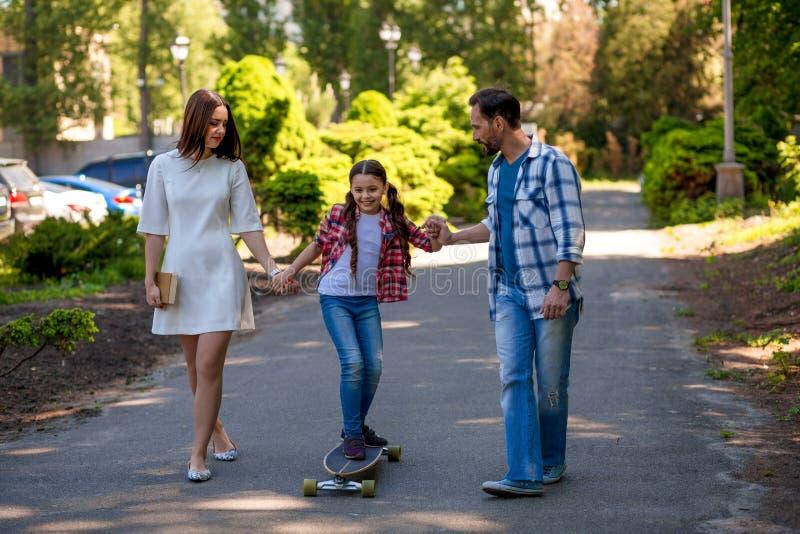 A menina está patinando no parque Mather And Fathert Are Holding sua filha imagens de stock